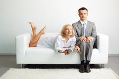 Seductive lady enjoying doing nothing lying on the sofa next to a serious busine Stock Photos