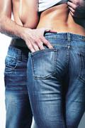 vertical shot of a seductive couple wearing jeans which accentuate beautiful for - stock photo