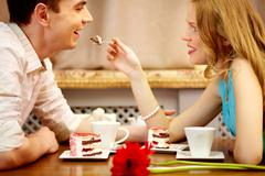 young people sitting in the cafe and eating dessert, girl shares the cake with h - stock photo