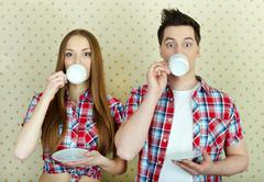 young couple drinking and looking at camera astonishingly - stock photo