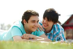 Happy gay lovers lying on the lawn Stock Photos