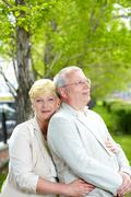 mature woman looking at camera while embracing her husband outside - stock photo