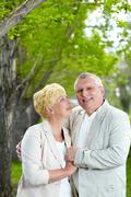 mature woman looking at her husband while having rest outside - stock photo