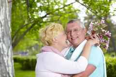 happy mature woman embracing her husband and touching his cheek by her nose - stock photo