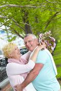 happy mature woman looking at her husband and both laughing in park - stock photo