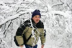 Man walking through snow filled branches Stock Photos