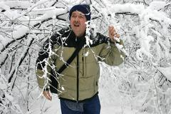 man walking through snow filled branches 2 - stock photo