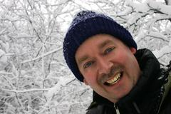 Man smiling to the camera while surrounded by snow filled branches Stock Photos
