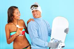 Portrait of cute girl in bikini holding cocktail with handsome man in pullover h Stock Photos