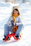 Portrait of happy mature woman sitting on sledge in winter Stock Photos