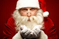 photo of kind santa claus with snow in hands looking at camera - stock photo