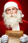 Portrait of santa claus holding christmas letter in his hands and looking at cam Stock Photos