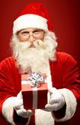 Photo of kind santa claus giving xmas present and looking at camera Stock Photos