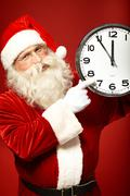 Photo of santa holding clock showing five minutes to midnight Stock Photos