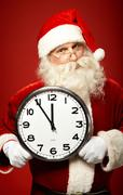 photo of santa holding clock showing five minutes to midnight - stock photo