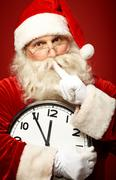 Stock Photo of photo of santa holding clock showing five minutes to midnight and making shhh ge