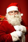 Portrait of happy santa claus holding sack with gifts and looking at camera Stock Photos