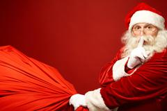 Portrait of santa claus with huge red sack keeping forefinger by his mouth and l Stock Photos
