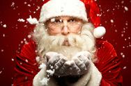 Stock Photo of photo of santa claus in eyeglasses blowing snow and looking at camera