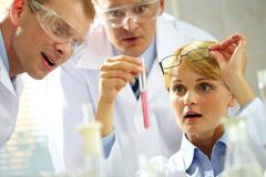 three inspired scientists looking at a substance discovered in a lab - stock photo
