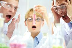 Three shocked scientists looking at the obtained substance expressing intense em Stock Photos