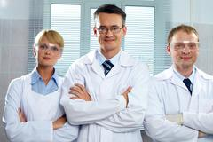 Three positive scientists looking at camera and smiling Stock Photos