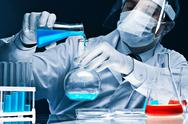 Stock Photo of masked male scientist mixing bright blue substances in glassware
