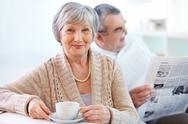 Stock Photo of portrait of mature woman with cup looking at camera on background of her husband