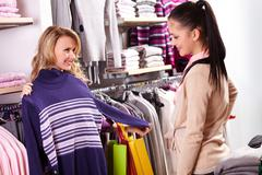 image of two pretty girls choosing clothes from new collection in department sto - stock photo