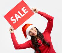 Happy girl in santa cap holds card with symbol of sale Stock Photos