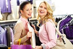 image of two pretty girls looking at camera while choosing clothes in department - stock photo