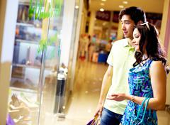 Tilt up of young couple standing in front of the shop window and looking at the Stock Photos