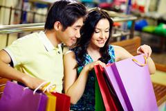 young woman and her boyfriend looking in the shopping bag with sweet anticipatio - stock photo