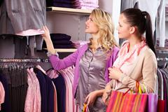 image of two pretty girls looking at new collection of clothes in department sto - stock photo