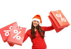 happy girl in santa cap holds red paperbags with symbol of discount - stock photo