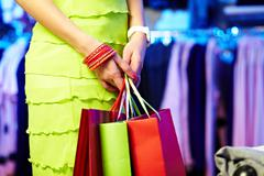 image of shopaholic hands with three shopping bags - stock photo