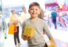 Portrait of happy child holding gift box with his family on background Stock Photos