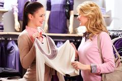 Image of two pretty girls choosing clothes from new collection in department sto Stock Photos