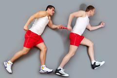 two guys taking part in a relay race passing the baton - stock photo