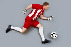 Determined soccer player dribbling the ball to score a goal Stock Photos