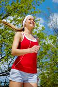 portrait of a young woman jogging with a walkman - stock photo