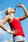 portrait of a young woman refreshing during workout - stock photo