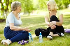 Senior women sitting on the grass and talking after a workout Stock Photos