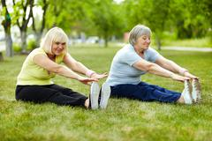 Senior ladies enhancing body flexibility by stretching Stock Photos