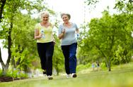 Stock Photo of portrait of two senior females running outdoors