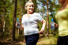 senior female with bottle of water running outdoors - stock photo