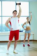 image of young man doing exercise with barbells with pretty girl on background - stock photo