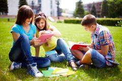 Söpö lukion opiskelijat tekevät läksyjä ulkona nurmikolla Kuvituskuvat