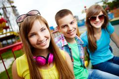 Teenagers spending time in the amusement park looking at cam with a smile Stock Photos