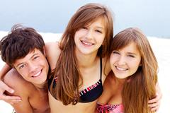 portrait of happy teenage guy and two pretty girls - stock photo